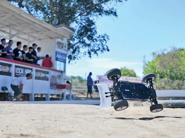 A remote controlled car jumps cover a hill on the racetrack at Hot Rod Hobbies on Thursday as drivers practice for the 17th Annual Hot Rod Hobbies and Raceways Offroad Shootout this weekend. Photo by Katharine Lotze/Signal