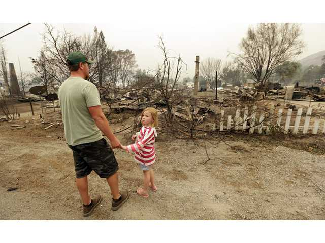 Forrest Harrison holds the hand of his daughter, Avery, 5, as he looks over the rubble remaining from his home after a wildfire destroyed it the night before Friday in Pateros, Wash.