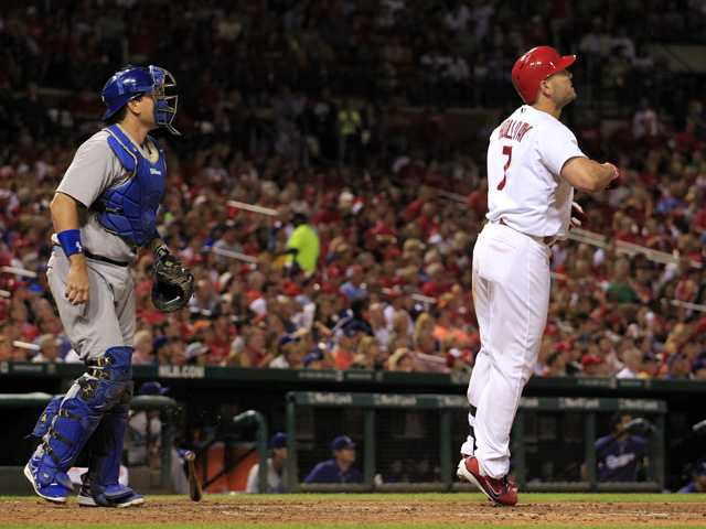 St. Louis Cardinals' Matt Holliday, right, and Los Angeles Dodgers catcher A.J. Ellis watch Holliday's two-run home run on Friday in St. Louis.