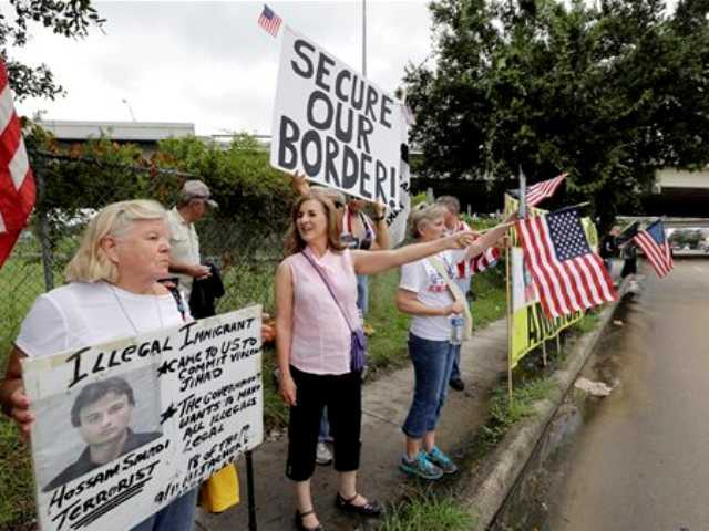 Demonstrators hold signs and flags outside the Mexican Consulate on Friday, July 18, 2014, in Houston. The sharp contrast in how Americans are reacting to the immigrant influx mirrors the divisiveness seen in Congress as the nation's leaders attempt to find solutions to an issue that could worsen in the coming months.