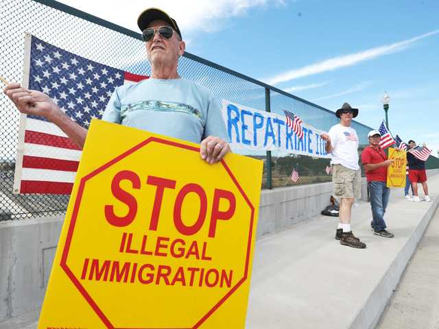 Richard Cowell of Valencia, left, holds a sign while standing with a small group protesting illegal immigration on Saturday.