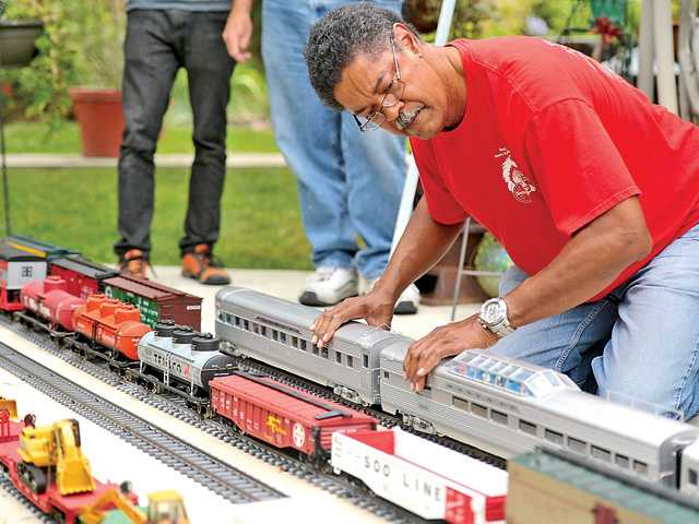 Allen Fuqua adjusts his miniature Santa Fe train at the Santa Clarita Valley Garden Railroad Club on Saturday.