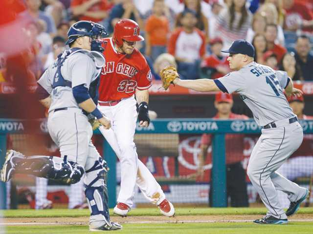 Los Angeles Angels' Josh Hamilton, center, is tagged out by Seattle Mariners third baseman Kyle Seager, right, during Saturday's game in Anaheim.