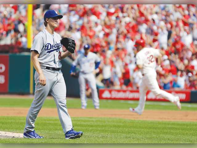 St. Louis Cardinals' Matt Adams, right, rounds the bases after hitting a two-run home run off Los Angeles Dodgers starting pitcher Zack Greinke on Saturday in St. Louis.