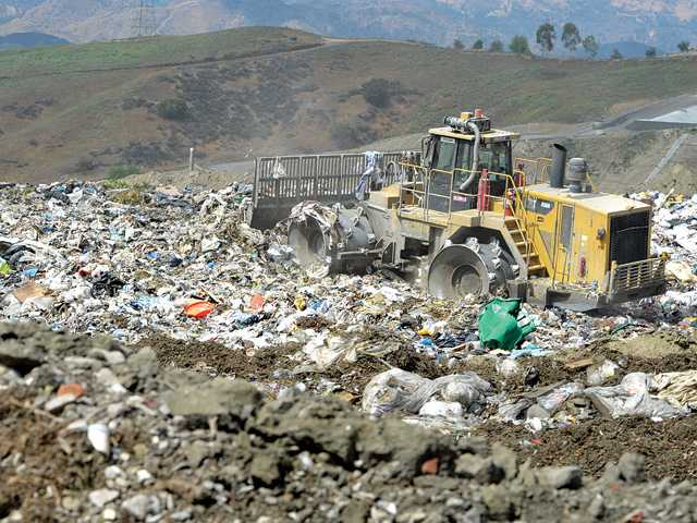 "A compactor rolls over the exposed trash at a 200 x 200 ""working face"" site at Chiquita Canyon Landfill. Ad soon as the trash is spread and compacted it is covered with dirt and the ""working face"" site moves forward. This view looks southwest toward the new proposed expansion site of the landfill. Signal photo by Dan Watson"