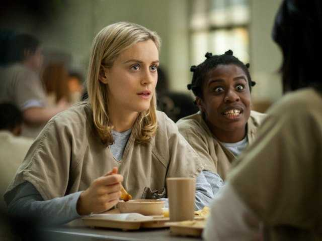 "This image released by Netflix shows Taylor Schilling, left, and Uzo Aduba in a scene from ""Orange Is the New Black."" Netflix reports quarterly earnings on Monday, July 21, 2014."