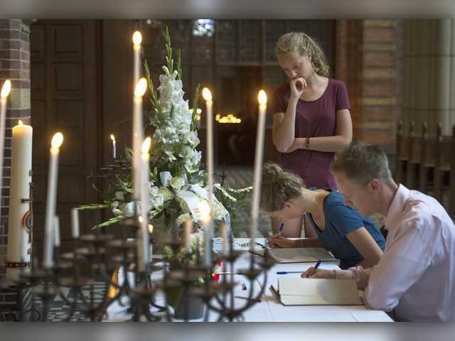 People sign a condolence register at St. Vitus church in Hilversum, Netherlands, Sunday, July 20, 2014. An attack on a Malaysian jetliner shot down over Ukraine on Thursday killed 298 people from nearly a dozen nations, more than half being Dutch.