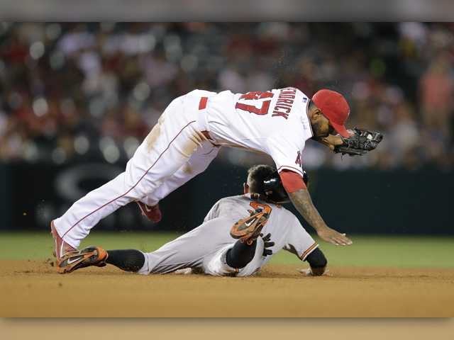 Los Angeles Angels second baseman Howie Kendrick, top, falls over Baltimore Orioles' David Lough after catching him stealing second base during the eighth inning Monday in Anaheim.