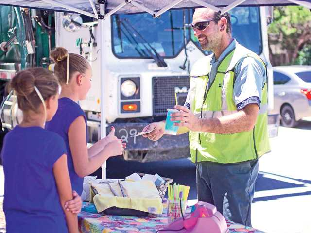 A local Waste Management worker buys some fresh lemonade from Sarah Wathen and Emily Widders at their stand in Newhall on Tuesday. Signal photo by Mitch Hacker.