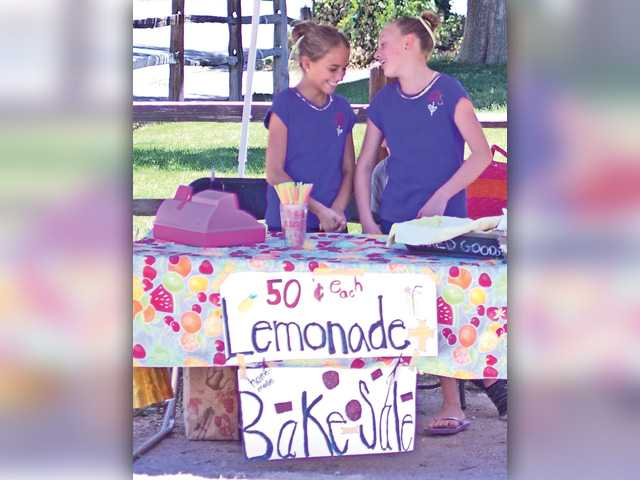 Emily Widders, left, and Sarah Wathen get ready to make more lemonade for potential customers at their Newhall stand on Tuesday. Photo by Mitch Hacker for The Signal.