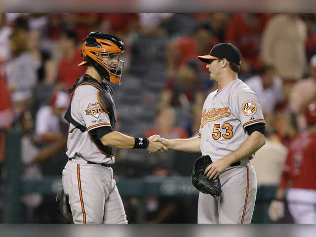 Baltimore Orioles catcher Caleb Joseph, left, and former Canyon player Zach Britton celebrate the team's 4-2 win against the Los Angeles Angels in Tuesday's game in Anaheim, Calif.