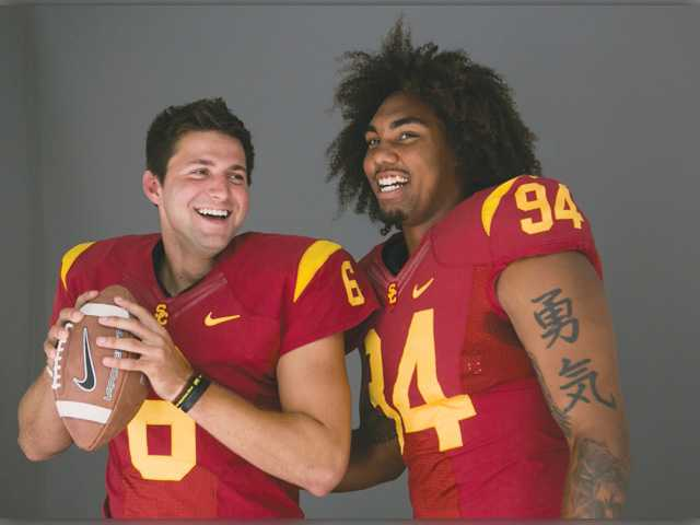 Universityt of Southern California quarterback Cody Kessler, left, and defensive end Leonard Williams pose for photos at the Pac-12 NCAA college football media days at Paramount Studios in Los Angeles.