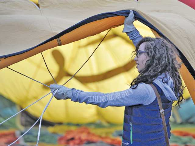 Volunteer Lucia Marquez holds open the mouth of the envelope of a hot air balloon as it is filled with cool air by a fan before launching at the Seventh Annual Citrus Classic Balloon Festival held in Santa Paula on Saturday. Signal photo by Dan Watson.