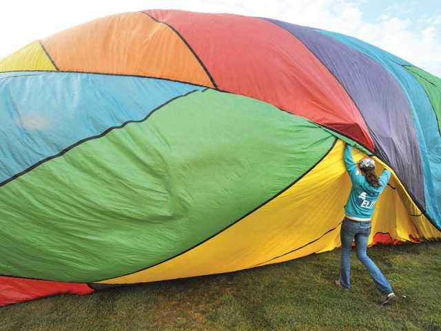 "A team member helps fill the ""Transition"" hot air balloon from Chino Hills with hot air in preparation for flight at the Seventh Annual Citrus Classic Balloon Festival held in Santa Paula on Saturday. Signal photo by Dan Watson."