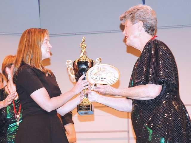 Christine Tavares-Mocha, left, director of Valencia High School's Chamber Choir, receives first-place trophies from Pat Kahmann, chairwoman of the 10th annual A Cappella Scholarship Festival hosted by the Verdugo Hills Showtime Chorus on May 17 at Glendale High School. Joyce Rudolph/Courtesy photo