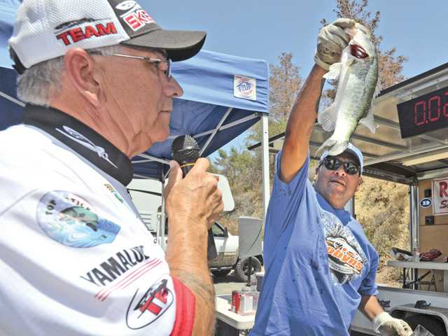 Event coordinator John Barron, left, prepares to call out weight as volunteer Erick Prado moves a fish to the scales to be weighed during the Wounded Warrior Project bass fishing tournament held at Castaic Lake on Saturday. Signal photo by Dan Watson.
