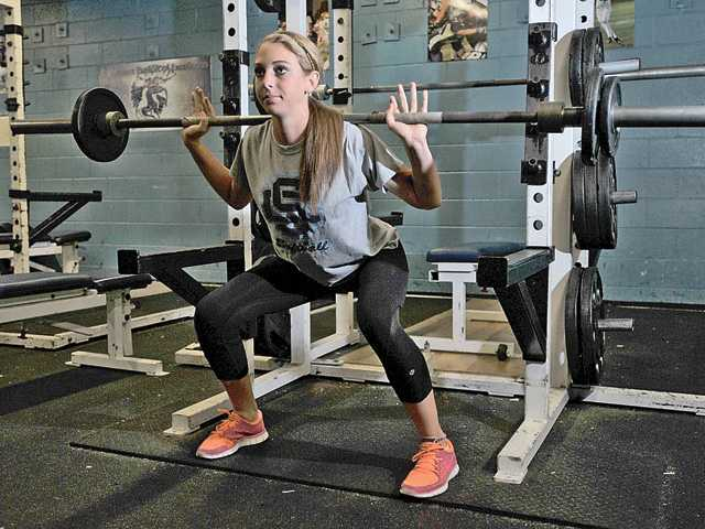 Saugus softball player Cayla Kessinger demonstrates proper squat form in the Saugus High School weight room on Monday. She is one of a growing number of female athletes beginning strength training in high school.
