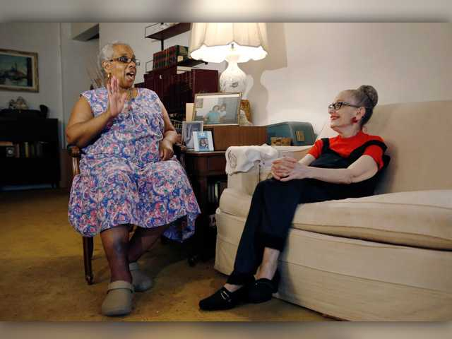 In this July photo, Carolyn Allen, left, recounts how she fell in the bathtub and was helped by roommate Marcia Rosenfeld, right, who owns the Brooklyn, New York apartment where Allen lives. The two women are roommates thanks to a home-sharing program run by a New York-based nonprofit agency.
