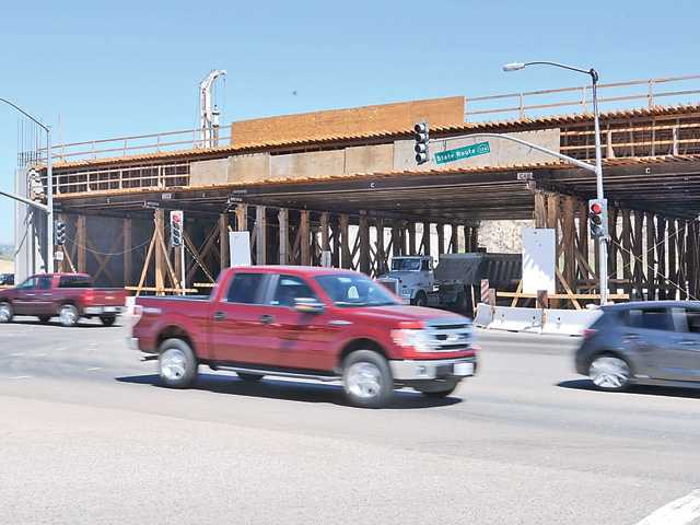Cars pass by the bridge under construction at the corner of Commerce Center Drive and Highway 126. Signal photo by Katharine Lotze
