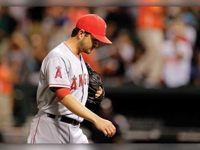 Los Angeles Angels relief pitcher Cory Rasmus walks off the field after Baltimore Orioles' Manny Machado hit a game-winning solo home run in the 12th inning of Tuesday's game in Baltimore.