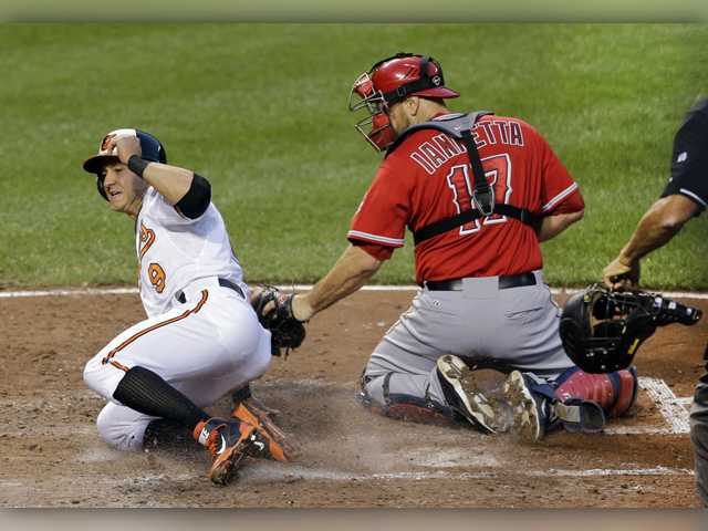 Los Angeles Angels catcher Chris Iannetta's tag is late as Baltimore Orioles' David Lough slides across home plate on a single by Ryan Flaherty in Wednesday's game in Baltimore.