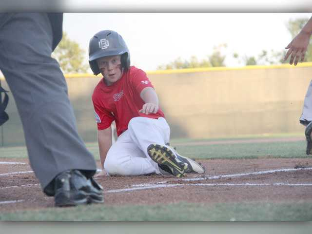 Jake Schwartz slides into home during the Hart 9U Red team's 7-2 win over North Valley in the Mustang-9 League Baseball World Series.