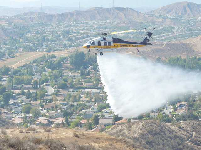 An L.A. County Fire Department water-dropping helicopter makes a drop near a five-acre fire that burned in a canyon south of Plum Canyon Road near Golden Valley Road and Suzie Lake in Saugus on Friday. Signal photo by Dan Watson