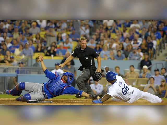 Los Angeles Dodgers' Yasiel Puig, right, scores on a fielders' choice by Hanley Ramirez as Chicago Cubs catcher Welington Castillo, left, reaches to tag him as home plate umpire Jim Wolf looks on during Friday's game in Los Angeles.
