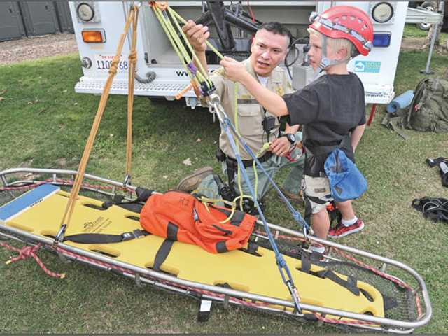 Dan Watson/The SignalJustin Warman, 8, right, of Castaic gets a demonstration of the equipment used by the Santa Clarita Valley Search and Rescue unit from Reserve Deputy Carlos Giron at National Night Out held at Central Park in Saugus Saturday.