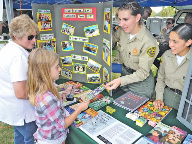 Dan Watson/The SignalDeputy Explorers Lauren Lockart, center, and Ally Heredia, right, hand out safety materials at the Santa Clarita Valley Sheriff's Station booth at National Night Out held at Central Park in Saugus on Saturday.