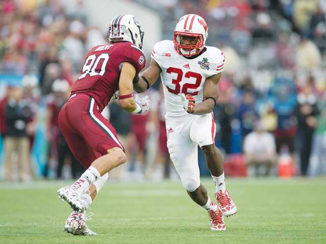 Golden Valley graduate and Wisconsin Badgers linebacker Leon Jacobs, right, runs down field during the Capital One Bowl against South Carolina on Jan. 1 in Orlando, Florida. Photo by Dave Stluka/Wisconsin Athletic Communications
