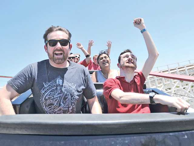 Jason Oliver, left, and Jonathan Oliver, right, brothers from San Diego, cheer as they ride Colossus at Six Flags Magic Mountain on Monday. Signal photo by Katharine Lotze