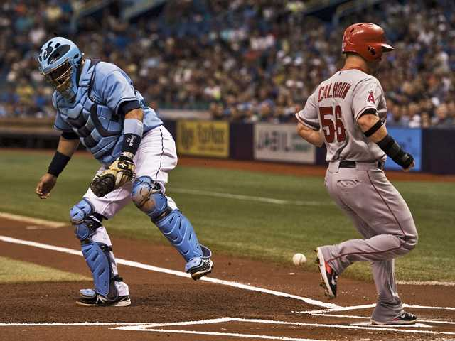The throw home skips past Tampa Bay Rays catcher Jose Molina, left, as Los Angeles Angels' Kole Calhoun (56) scores on Mike Trout's RBI-double on Sunday in St. Petersburg, Fla.