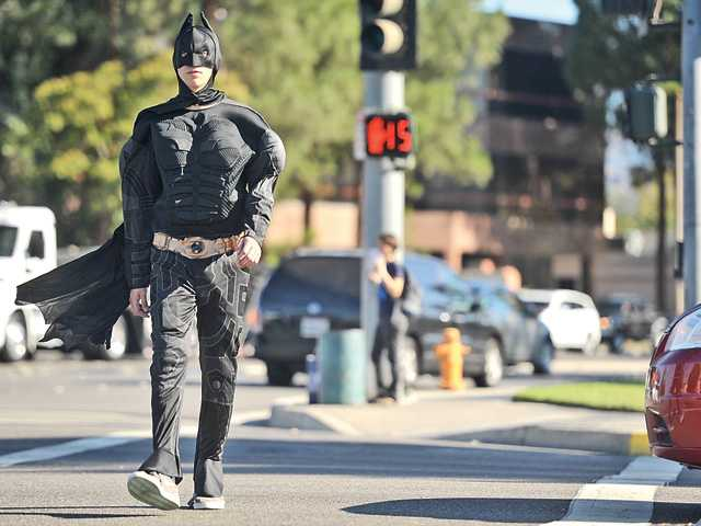 Brett Turk, 18, a member of the Sheriff's Explorer program, dressed as Batman, crosses Magic Mountain Parkway at Valencia Boulevard during a crosswalk enforcement operation to attempt to cut down on pedestrian vs. vehicle accidents at crosswalks in the SCV on Monday. Signal photo by Katharine Lotze.