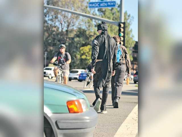 Brett Turk, 18, a member of the Sheriff's Explorer program, dressed as Batman, crosses Magic Mountain Parkway at Valencia Boulevard during a crosswalk enforcement operation on Monday. Signal photo by Katharine Lotze.