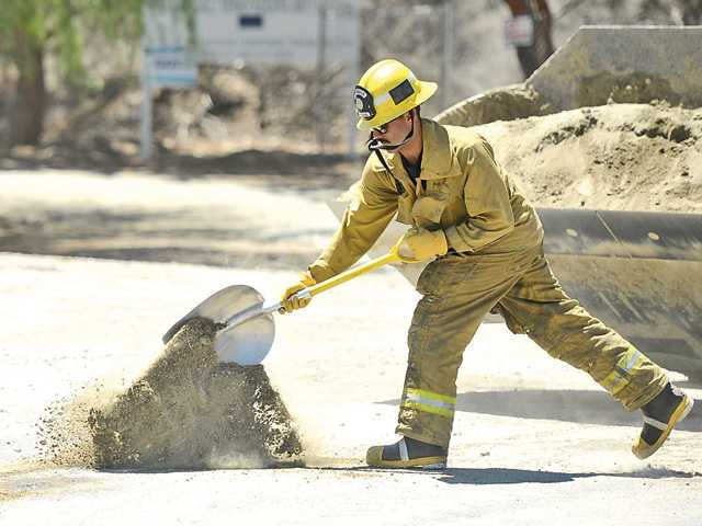A fireman shovels dirt over gas spilled from a semi after it was hit by another vehicle on Soledad Canyon Road. Signal photo by Katharine Lotze.