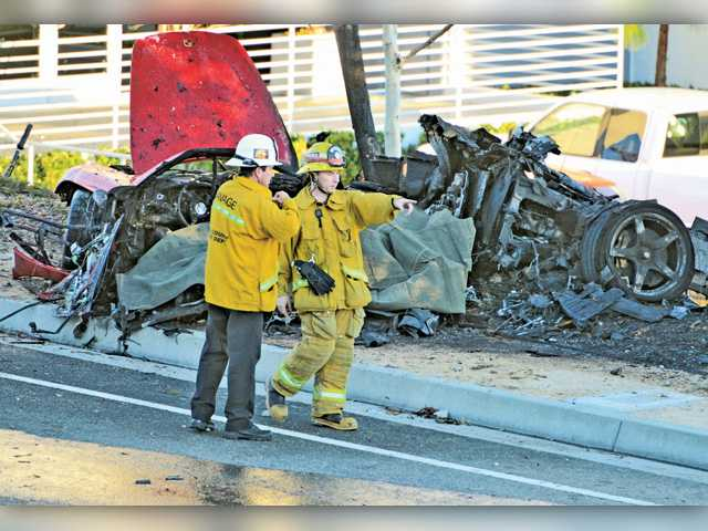 "First responders gather evidence near the wreckage of the 2005 Porsche Carerra GT in which ""Fast and Furious"" star Paul Walker and Valencia businessman Roger Rodas died on Nov. 30. Dan Watson/Signal File Photo"