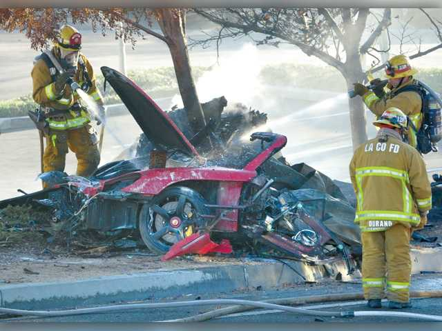 "Firefighters spray water on the wreckage of a Porsche that crashed into a light pole and a tree on Nov. 30, killing ""Fast and Furious"" star Paul Walker and Valencia businessman Roger Rodas. Dan Watson/Signal File Photo"