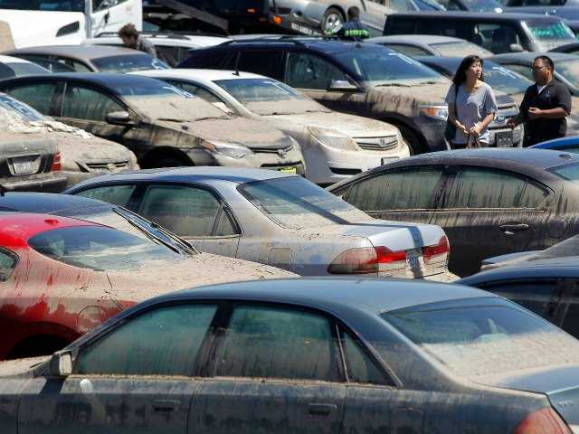 Car owners pick up personal property from their cars Tuesday, Aug. 5, 2014, that were damaged and recovered from a parking structure that flooded after a water main break July 29, on the UCLA campus in Los Angeles.