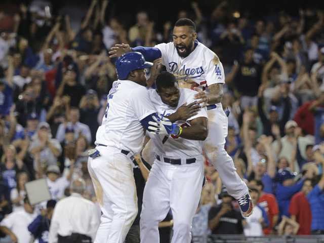 Los Angeles Dodger Juan Uribe, left, Yasiel Puig, center, and Matt Kemp, top, celebrate after Uribe scored the winning run against the Los Angeles Angels on Tuesday in Los Angeles.