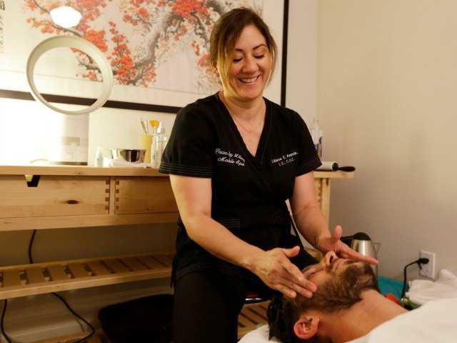 In this photo taken Tuesday, July 29, 2014, Liliana Aranda, owner of Faces by Liliana, does a peppermint neck and scalp treat to Dr. Austin Davis at his chiropractic office in San Francisco.