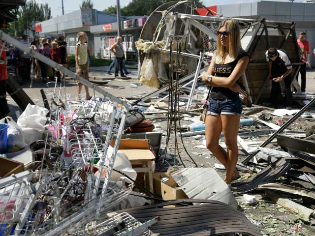Residents inspect the damage after night shelling on a market in Donetsk, eastern Ukraine, Wednesday.