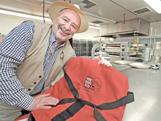 "Santa Clarita Valley School Food Services Agency retiring CEO Pavel Matustik displays a pizza-carrying bag bearing the name ""Papa Pavy's Pizza,"" along with his characature, in an agency kitchen. Matustik is retiring after 21 years. Signal photo by Dan Watson"