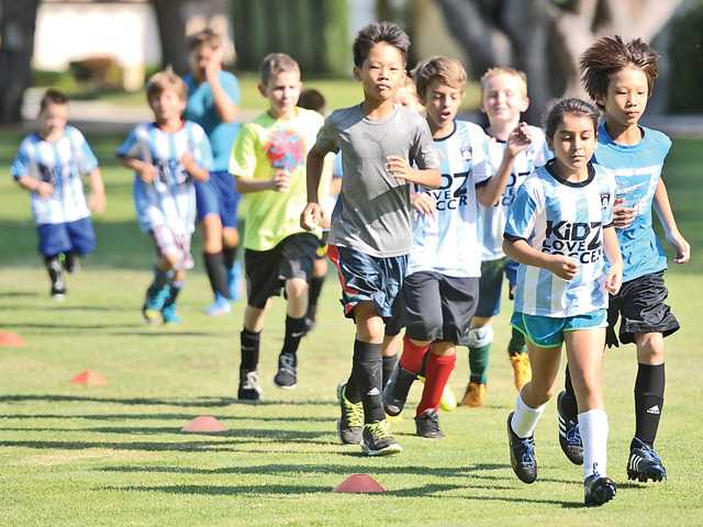 Young soccer players take their warm-up job around the field at the Kidz Love Soccer summer camp at Valencia Glen Park this week. Signal photo by Katharine Lotze