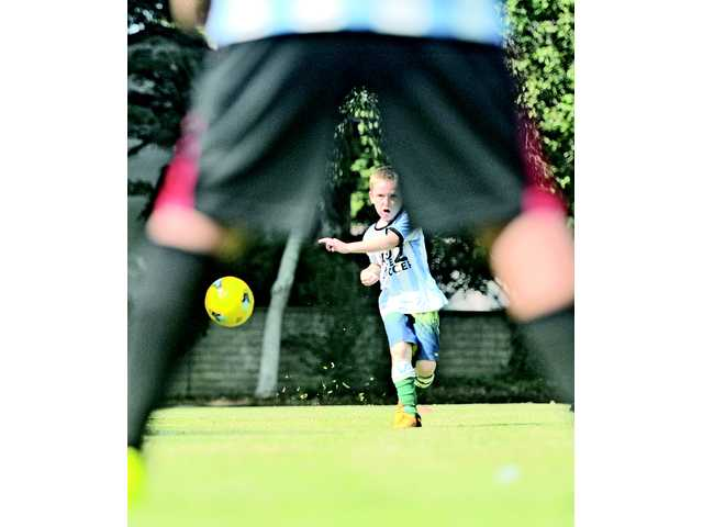 """Matthew Cole, 7, kicks the ball in an attempt to make it through the legs of teammate Sean Sendewicz, age 9, in a game called """"bullseye,"""" which helps kids improve their aim, during Kidz Love Soccer camp at Valencia Glen Park this week.Signal photo by Katharine Lotze"""