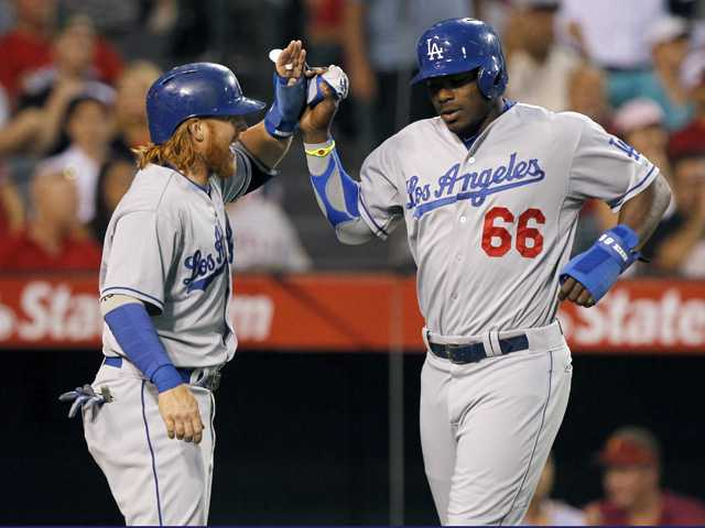 Los Angeles Dodgers' Justin Turner, left, congratulates Yasiel Puig during Thursday night's game against the Los Angeles Angels in Anaheim.