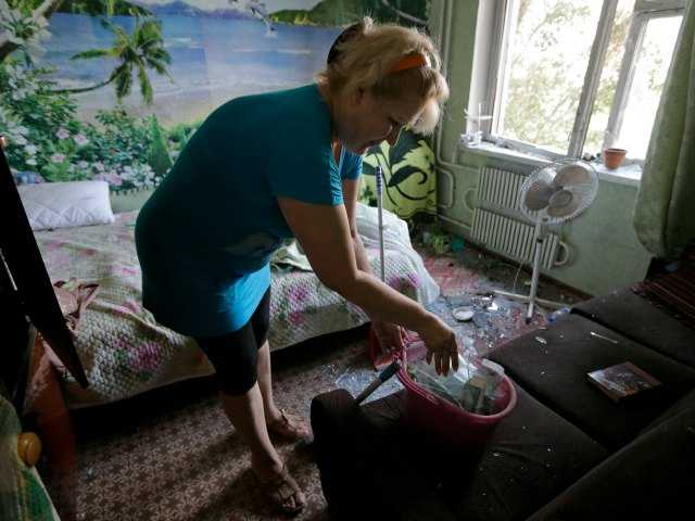 Marina Barsuk clears broken glass inside her apartment after overnight shelling in Donetsk, eastern Ukraine, Friday, Aug. 8, 2014.