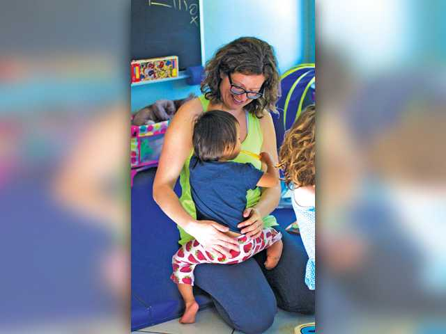 Angie Ashe holds her 2-year-old daughter Fiona in their home in Valencia. Austin Dave/The Signal