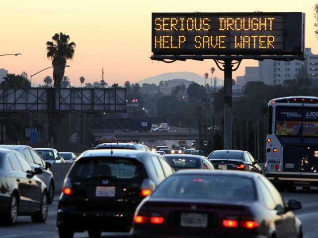 In this Feb. 14, 2014, file photo, morning traffic makes it's way toward downtown Los Angeles along the Hollywood Freeway past an electronic sign warning of severe drought.