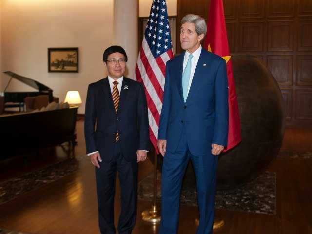 U.S. Secretary of State John Kerry, right, meets with Vietnam's Foreign Minister Pham Binh Minh, left, at a hotel during their meeting outside the venue of the 47th ASEAN Foreign Ministers' Meeting in Naypyidaw Saturday, Aug. 9, 2014.